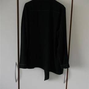 Varetype: Tunika Skjorte Farve: sort m/hvide stikninger Oprindelig købspris: 2499 kr.  Flot og fed tunika med de fine detaljer fra Ivan G. Brystlomme, og en ½ skjorte syet udenpå tunikaen, som gør tunikaen speciel & længere i højre side både foran og bagpå, samt lange ærmer..   Materiale er: 100% Polyester.   Mål er: Længden i venstre side 79 cm (foran hvor tunikaen er alm) Længden i højre side 96 cm (foran hvor der er syet en ½ skjorte udenom) Brystmål 2 x 59 cm   Hvis du vil have den sendt udenfor DK må dette aftales med sælger.    ¤¤¤ BYTTER IKKE ¤¤¤