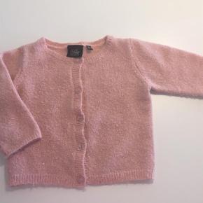 Varetype: Cardigan Farve: Rosa Oprindelig købspris: 300 kr.  Super fin strik cardigan med små fine lurer tråde i glimmer rosa. Materiale: 50% akryl, 32% nylon, 10% uld, 5% metallic garn, 3% spandex.  Ved Ts handel betaler køber gebyret