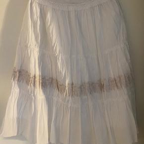 Smuk nederdel fra Kenzo's junior kollektion, som er både rå og feminin på samme tid.  Har rå kanter, samt broderi med blomster fortil. Str. 16 junior Bredde 35 cm. øverst Længde 74 cm.