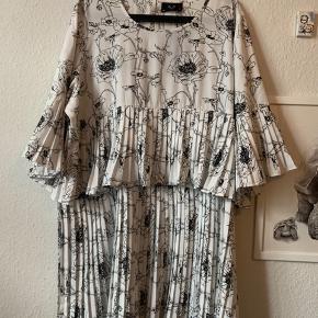 AX Paris Plus Tiered Floral Dress  Hvid kjole med sort print. Aldrig brugt, stadig med mærke. NP: 472 kr BM: 64 cm x 2  L: 96 cm  Jeg bytter ikke.   ⭕️ OBS. Pga. Stram skema lige pt, kan jeg først sende pakker i weekenderne.
