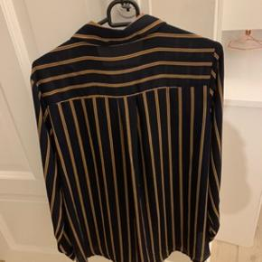Flot trendy Only skjorte i blå/rust striber med fine detaljer i form af guldknapper. Stand: fremstår som ny og har kun været i brug 1 gang i få timer. Nypris: 399