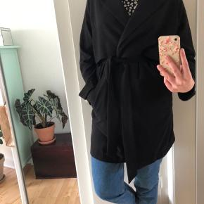 Fin sort frakke med knapper og bindebånd i taljen. Den er normal i str., jeg er 180 høj til sammenligning. God overgangsjakke eller med en strik indenunder, når det bliver køligere. Skriv, hvis du har spørgsmål :)