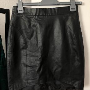 Læder-look nederdel str.s. Brugt nogle gange, men i ok stand. Passes af en normal str.s. Ingen billeder med den på
