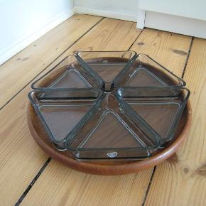 Retro teak anretningsfad, Holmegaard Kastrup. Anretnings/ snack fad i teaktræ fra 50'erne med 6 glas skåle, i en rigtig fin stand, der er dog et sted på den tynde kant hvor man kan se at der er en lille flig, der er slået af på en af glasskålene. Diameter på teaktræs fad 27,5 cm