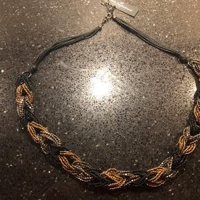 Flettet halskæde i mørke/gyldne nuancer, lavet af glas og metalperler.   Ny og ubrugt med tags.