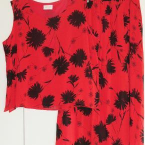 Norbelle: Sæt: bluse + nederdel Farve: Rød med sorte roser  100 % NY: Lækkert sæt i rødt med sorte roser. Sættet er i to tynde lag (men ikke gennemsigtigt). Blusen har 8 cm høje slidser i begge sider. Oprindelig købspris: 1200 kr.  Blusen: Brystvidde: 63 cm x 2 Hoftevidde: 63 cm x 2 Længde: 64 cm.    Nederdel: Elastik-liv: Mellem 45-61 cm x 2 Længde: inderste lag er 82 cm og yderste lag er 87 cm.  Ingen byt, og prisen er fast.