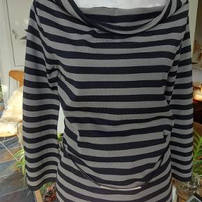 """Varetype: Sød stribet bluse som ny Farve: sort og grå  Super sød bluse/shirt - str. L - stribet i sort/grå fra Joseph A. (købt i USA)  7/8 ærmer (let trompetfacon)  Flot """"vandfalds""""-udskæring  Smalt, dobbelt lædersnøre-bælte som pynt (se billede)  65% viscose - 35% nylon  Brystvidde 46 cm x 2 (liggende fladt) Ærmelængde 53 cm Længde 60 cm  Kun brugt få gange og er som ny :-)  Handler gerne via MobilePay og sender (helst) med DAO"""