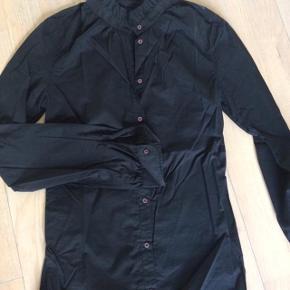 Smuk sort facon syet skjorte. Lidt høj i halsen med rynke effekt. Meget elegant.  Brugt 1-2 gange.