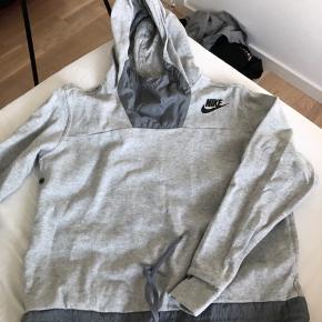 Sweater fra Nike med hætte, lommer foran og en snor i bunden det kan strammes ind.  Stoffet er lidt fnuldret foran, men ellers fejler den ikke noget 😃 Byd gerne!