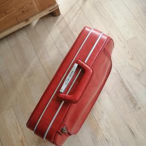 Flot rød retro / vintage kuffert med en lille lås (uden nøgle), har et stort runt der åbnes og lukkes med lynlås og en lomme bagpå. Er i fin stand, men har nogle brugsspor.