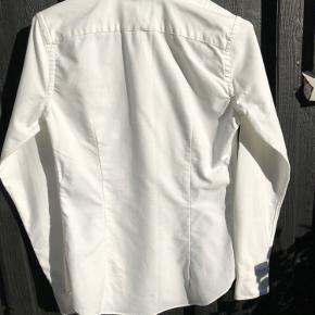 Klassisk hvid skjorte i slim fit fra Ralph Lauren. Brugt få gange derfor i fin stand.