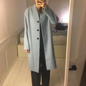 Lyseblå frakke i uld. Brugt en enkelt dag til et photoshoot. Sælges for 180 kr. Se frakken i videoen på forsiden af www.lemonsuite.dk . Str. 36 / S. Kan afhentes i Kbh K.