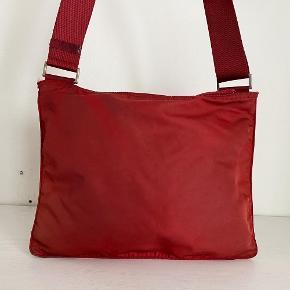 Lidt om tasken 👜 Flad Prada taske i en fin mørkerød farve. Stroppen er justerbar.  Der medfølger desværre ikke noget til tasken   Stand 💬 Standen på den e taske er god men brugt, der er en del slid og mærker på tasken. Her er der tale om en del pletter på forsiden, misfarvning i hjørnerne af tasken samt logoet der er gået en lille smule op.   Autencitetsgaranti ☀️ Alle tasker autencitetstjekkes inden salg, vha. specifikke indikatorer på tasken som kan vise om den er ægte. Du kan derfor være tryg ved, at du investerer i et autentisk produkt!  Kun seriøse bud tak 🙌  Mængderabat gives ved køb af flere ting✨