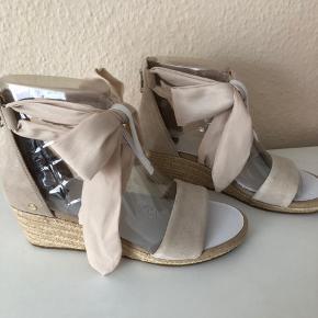 Superfine sko med kilehæl fra UGG AUSTRALIA. De højhælede sko er fremstillet i ruskind og har en fin dekorativ sløjfe rundt om anklen. – Lynlås ved hælen Hælhøjde: 5 cm Plateau: 2 cm. Nypris 969kr Mp 600kr + fragt