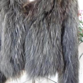 Flot Vaskebjørns Pels sælges, den lukkes med en hægte str. S/M  Bytter ikke.  Brystmål: 51x2   Længde:53 cm. Farve: gråbrun. Handler over mobil pay med denne-    Sælges for mit barnebarn. .