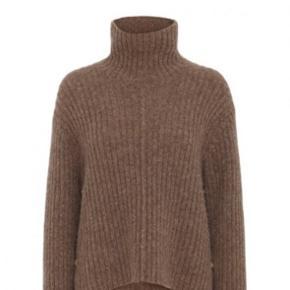 Sweateren er en rullekrave strik i camel med guld knapper i siderne, den er brugt 2 vintre primært, men er i fin stand