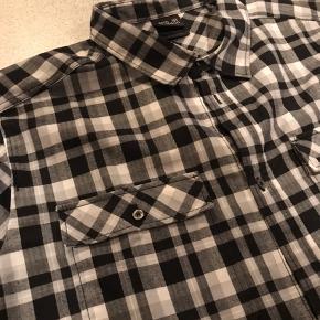Fin sort, grå og hvidternet skjorte.