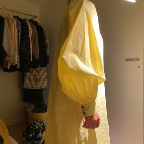 Super lækker, gul kjole fra Gestuz. Fin længde, v hals og med pufærmer. Aldrig brugt, men vasket og har været lagt sammen (derfor krøllerne). (Bindebælte mangler)  Byd. (Købt på udsalg til 900kr)