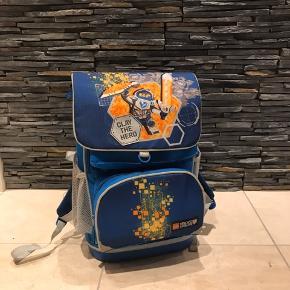 Brugt 1 sæson Virkelig lækker taske fra Lego Med lille gym taske der kan klikkes på skoletasken.  Og fint rum til madpakken. Fra IKKE ryger hjem og hjem UDEN dyr