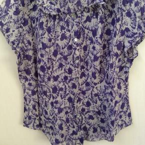 Tynd og let bomuldsskjorte med perlemorsknapper og et lille ærme. Længde fra skulder og ned 69 cm Brystmål 114 cm Taljemål 100 cm