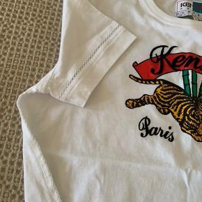 Ikonisk Kenzo t-shirt sælges. Størrelsen er 38, men passes bedst af en 36. T-shirten bærer det klassiske Kenzo-logo, og har de fineste blondedetaljer langs kanterne. Har kun været i brug én gang. Nypris var 799,-