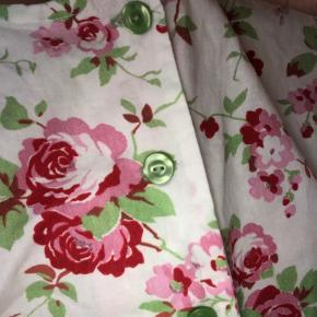 Sød vintage top i hvid med knapper i limegrøn, blomster mønster i lyserød, rød og grøn. Toppen har T-shirt ærmer og bindebånd om maven, kan bindes på forskellige måder. Den er en smule længere bagpå. Passes af S - M måske anden da den kan justeres ved taljen.