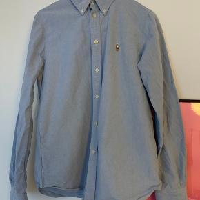Polo Ralph Lauren Skjorte i custom fit. Aldrig brugt. Der tages ikke billeder med skjorteN  på 😊. Nyprisen var 800 kr. Kom gerne med et bud!  Jeg bytter ikke.  God mængderabat gives - så tjek mine andre annoncer 🌸
