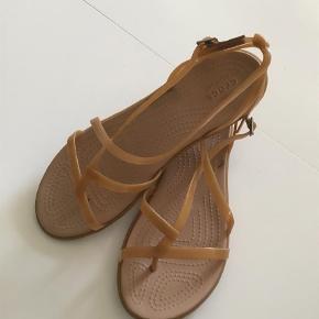 Varetype: Sandaler Størrelse: 38.5 Farve: Guld Oprindelig købspris: 275 kr.  Super fine sandaler fra crocs i guld , str w8 syntes den svare til 38,5/39   Utrolig blød og fleksibel at have på , kan skylles under hanen og tørre på 2 minutter  Mål cirka 25 cm  Bytter ikke kom med et bud