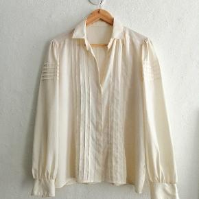 Vintage skjorte i cremet hvid med flæser.  Materialet er polyester.  Fremstår som ny.  Passer str. S/M.