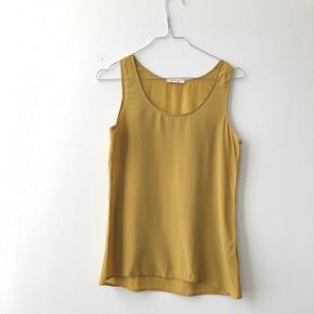 Smuk top i 100 % silke fra American vintage. Størrelse small. Farven er helt særlig og meget guld skær.
