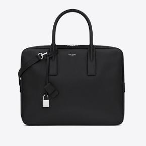 """Sælger denne lækre briefcase fra YSL / Yves Saint Laurent. Det er den store model, med plads til en 15"""" computer. Den er meget sparsomt brugt, og fejler intet. Alt følger med til den (Dustbag, kvitt osv). Byd gerne! Flere billeder kommer snart"""