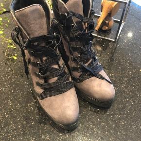 Virkelig smuk og anderledes snørrestøvle i ruskind fra Unisa med kilehæl.  Hælhøjde 8,5 cm.  Aldrig brugt.