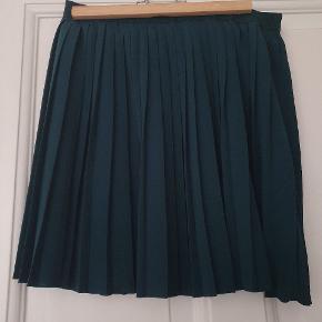 Cool mørkegrøn nederdel, der går lige over knæet.