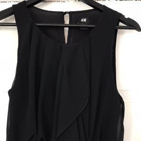 Flot sort kjole fra H&M str. 38 med flæsedetalje foran. Knaplås i nakken.