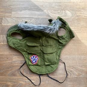 Armygrøn hundejakke med velcrolukning på maven. Fremstår i god stand, er vasket et par gange og har fnuller i velcroen. Hul til snor på ryggen under hætten, hætten kan tages af. Der er påsyet sorte elastikbånd til at gå om benene, disse kan fjernes hvis man ikke bryder sig om det.  Kan ikke huske præcis str, men mener det er en str S.   Mål:  Længde på ryggen: 29 cm  Tværs over bryst ved hals: 39 cm Tværs over mave: 50 cm
