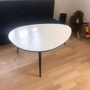 Hvidt lakeret sofabord med sorte ben fra BoConcept.  Længde: 111 cm og 78 cm bredt.   Der er nogle små hvide mærker på benene, og et større hvidt lakeret mærke på bordet. Bordet er fra 2014 og der er spor efter brug, men er ellers fint.