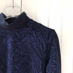 Bluse med lynlås i nakken. Sort/blå-brokade-stof der er lidt elastisk. Den kan sagtens passe en M også.
