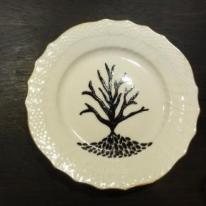 Dekoreret vintage tallerken. Royal Copenhagen dekoreret med porcelænsfarve. Farve : hvid / guld / sort. Ø: 15,5