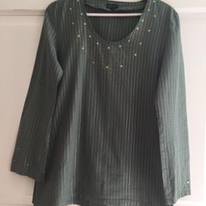 Yndig skjorte / tunika støvet grøn med tynde guldtråde, perler og diskret print. Str. M (40/42). Let figursyet. Perler kan nemt pilles af, hvis man ikke synes om dem. Sendes gerne. Køber betaler porto.