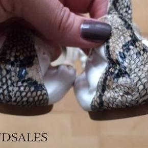 Varetype: Ballerina sko Størrelse: 38-39 Farve: Se tekst Oprindelig købspris: 600 kr.  Fine ballerina sko med stretch i kantåbningen. Hvide med slangeskind på skosnuden og bagpå hælen.  De fremstår næsten som nye indeni og udenpå, dog kan man se på sålen at de er blevet gået med udenfor. Hælene er meget fine.  Jeg bruger normalt str. 39, men disse ballerinaer er i str. 40. Ballerina skoene er købt i en af de små butikker i Latiner kvarteret i Aarhus.  Jeg sælger også en fin Minimum kjole som passer godt til disse ballerina sko. Se billeder i Billedgalleri.