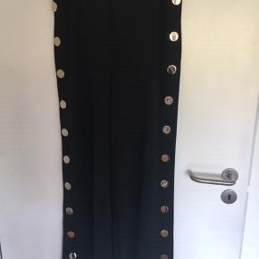 Nye og ubrugte bukser stadig med tags i st. 38. Taljen måler: 2 x ca. 38 cm materialet er: 73% Polyester, 22% Viskose og 5% elastan. Knapperne er: guldfarvet. Knapperne kan ikke knappes op. Nypris kr.  399,00 MP 150,00 pp