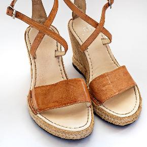 """Sandaler, str. 38, scarpa, Lys cognac, Læder, Næsten som ny Sandaler, str. 38, fra Scarpa Shoes , lysebrunt læder, God stand, kun brugt få gange. Vintage! Wedge sandals fra italienske Scarpa shoes, i lysebrunt læder og """"cross over"""" i lukningen. Hælhøjde:Ca.10 cm. Har købt sandalerne for næsten 20 år siden hos Scarpa Shoes. Har derfor ikke længere en kvittering. flot & i velholdt stand, da de i mange år bare har ligget ubrugt i en skoæske. Disse billeder er ikke reklamefotos, men taget af min kæreste, der er fotograf. Accepterer ikke PayPal."""