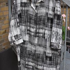 Storskjorte fra In Wear i fed viscoseagtig kvalitet, med lille drengekrave, langt 3/4 ærme med manchet og gennemknappet med skjult lukning. stor str. 36.  Kan bruges med stramme bukser eller strømper.  kjole Farve: sort/hvid Oprindelig købspris: 999 kr. Nu: 75 kr.