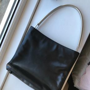 Smuk 90'er Prada håndtaske købt på Vestiaire Collective. Der er nærmest ingen tegn på slid. Tasken har en del praktiske rum indeni og mange smukke detaljer. Jeg kan sende flere billeder ved interesse. Kom gerne med et bud.