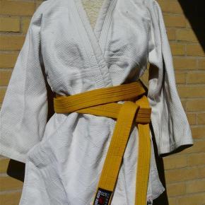 Judo jakke med gult bælte. Ekstremt tyk stof. Fejler intet, men trænger til en vask, defor sat til 'God men brugt'.  Judo jakke / kampsport med bælte Farve: Hvid