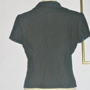 Varetype: Med kort ærme. Farve: Sort Oprindelig købspris: 500 kr.  Lækker bluse/jakke fra Vila. Den er med et let foer.  Brystvidde: 46-50 cm x 2 (dyb V-udskæring, som kan åbnes mere eller mindre) Livvidde hvis den er knappet: 43 cm x 2 Hoftevidde: 48-50 cm x 2 Længde: 58 cm   Ingen byt, og prisen er fast.   Forsikret forsendelse med TS's samarbejdspartner DAO. Hvis du ønsker anden forsendelse, så bare sig til.