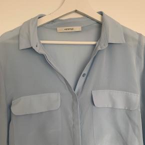 Smuk, lang skjorte i tyndt silke-stof, lidt gennemsigtigt.  Syet en anelse ind i siderne, da den var meget stor i størrelsen, nu er den mere størrelsessvarende.  Kun brugt er par gange, dog lidt krøllet af at have været foldet.