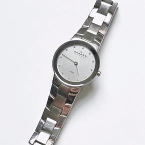 Uret er i god stand, og fungerer perfekt. Uret har få brugsspor på remmen, men ingen store skader.  Remmen måler 21 cm. om håndledet, som den er - men det kan godt afkortes.