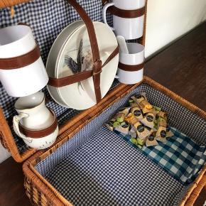 Frokost i det grønne - med toner af blåt :)   Tag på picnic med dem du holder af - indeholder  3 tallerkener af porcelæn - fuglemotiver.  3 plastik kopper. (Ikke engangs) 3 plastik skeer. (Ikke engangs)  1 flødekande af porcelæn.  En tynd plastik dug i blå/hvide tern.   Lavet af flettede grene, conac læderremme, messing lås og foret med blå/hvidternet stof.   46x30 cm og 20 cm høj.