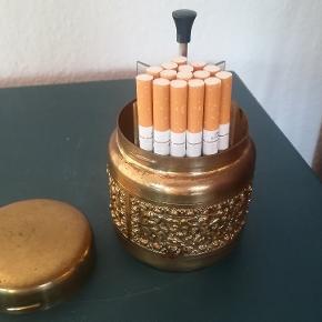 Gammel flot cigaret holder fra 1950 /60er. Messing. Højde Ca. 9 cm. Diameter Ca. 9 cm. Der er plads til Ca. 15 stk. Cigaretter i hver af de 4 rum i alt 60 stk. Har lidt patina se billeder. Kan afhentes i Århus N. /Trøjborg